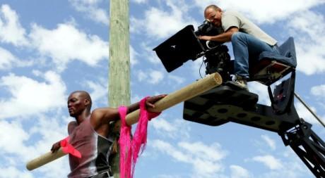"""A la caméra Sarel Eloff qui filme l'acteur Andile Kosi pendant le tournage du film """" Jezile"""" en 2005.  Reuters/Mike Hutchings"""