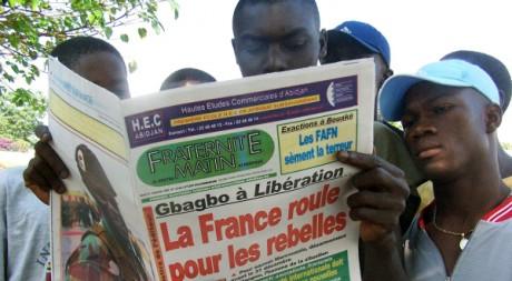Des Ivoiriens lisent un journal à Abidjan, 16 novembre 2004, REUTERS/Stringer
