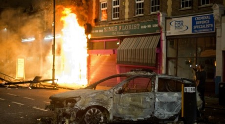 Une  boutique et une voiture brûlée pendant les émeutes de Tottenham, 6 août 2011. © Leon Neal / AFP