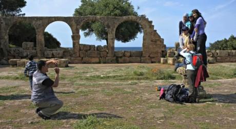 Un homme prend en photo des touristes à Tipasa, Algérie © Zohra Bensemra / Reuters