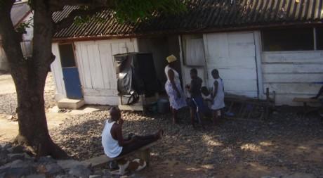 Le fils ainé d'Adjo écoutant la radio pendant que sa mère s'occupe de ses petits enfants © Bruno Sanogo, tous droits réservés