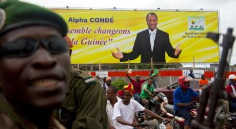 Un gendarme devant une affiche électorale du candidat Alpha Condé, à Conakry 19 octobre 2010, REUTERS/Stringer