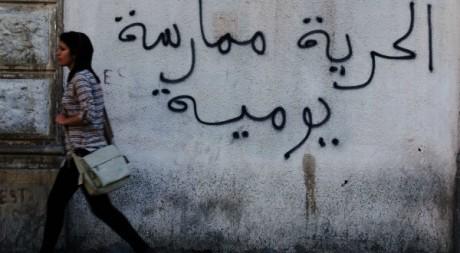 """Une jeune fille passe devant une inscription:""""la liberté, une pratique quotidienne""""Reuters"""