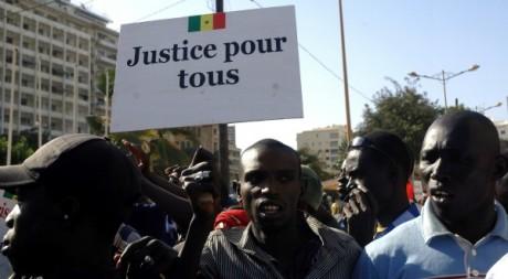 Un Sénégalais tenant une pancarte lors des manifestations le 19 mars 2011. AFP/Erick Christian Ahounou