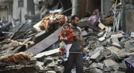 Un père et sa fille dans des ruines à Gaza, le 25 novembre 2012. REUTERS/Mohammed Salem