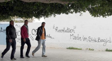 Des Tunisiens devant un mur de graffiti à Sidi Bouzid, décembre 2012. ©KHALIL / AFP