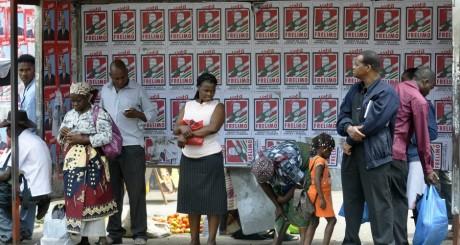 Des gens attendent un bus à Maputo, devant des affiches électorales, 27 octobre 2009. REUTERS/Grant Lee Neuenburg