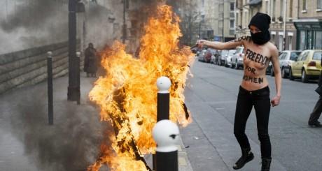 Une membre des Femen brûlant le drapeau salafiste, Paris, 3 avril 2013 / AFP
