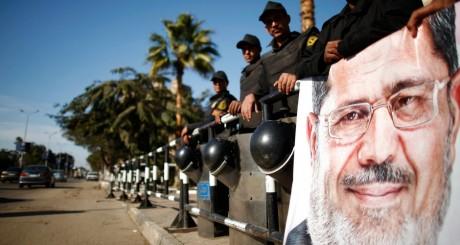 Policiers tenant une affiche de Mohammed Morsi, Le Caire, décembre 2012 / REUTERS