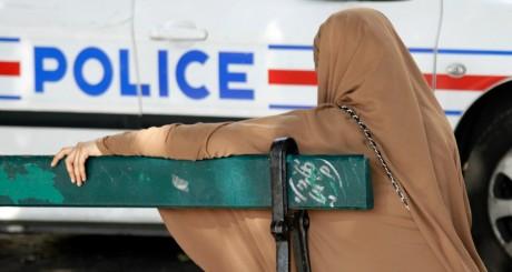 Voiture de police passant devant une femme voilée, France  / Reuters
