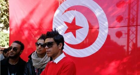 Des jeunes devant un drapeau tunisien pour le deuxième anniversaire  de la révolte à Tunis, 13 janvier 2013 / REUTERS