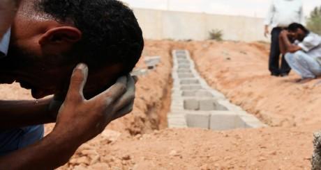Des rebelles libyens pleurent la mort d'un des leurs, tué par les forces de Kadhafi, 25 août 2011 / REUTERS