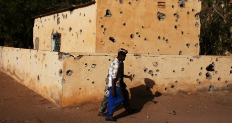 Deux hommes devant un bâtiment criblé de balles à Gao, 13 mars 2013 / REUTERS