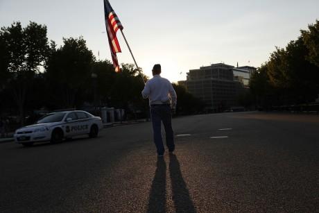 Un ex-légionnaire américain porte un drapeau devant la Maison Blanche. REUTERS/Jonathan Ernst