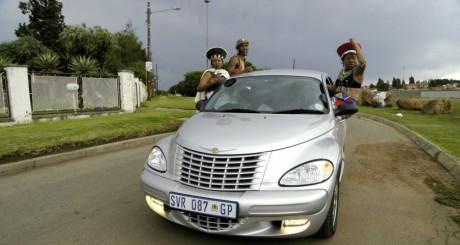 Des habitants d'un township posant sur une voiture de luxe / Reuters