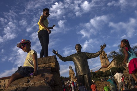 Des touristes posent à côté de la statue de Nelson Mandela à Pretoria. REUTERS/Adrees Latif