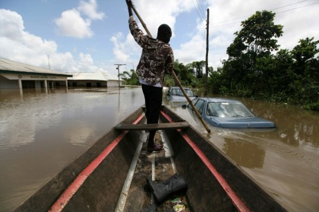 Un homme traversant la ville de Patani au Nigéria en pirogue après les inondations de 2012, REUTERS/Afolabi Sotunde
