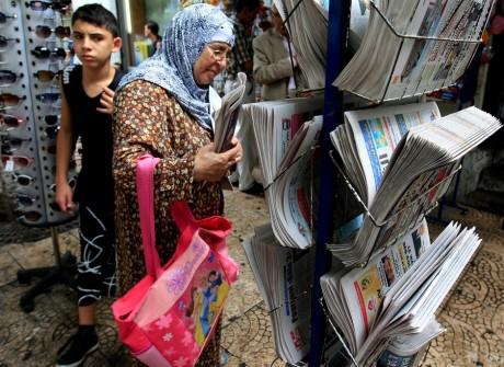 Une Algérienne achetant un journal à Alger, REUTERS / Zohra Bensemra