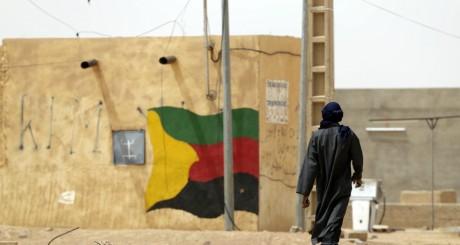 Un Touareg passant devant un mur aux couleurs du MNLA, Kidal / AFP