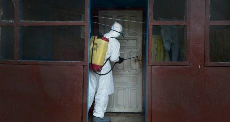 Un agent de santé décontamine une poignée de porte , Monrovia. © Kieran Kesner via Mashable