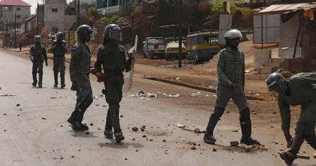 Des policiers ramassent des pierres lancés par des manifestants à Conakry, le 7 mai 2015. REUTERS/Saliou Samb