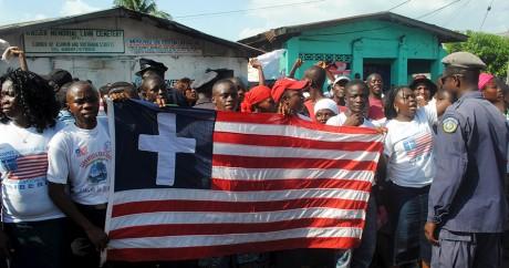 Des habitants du Liberia brandissent un drapeau du pays où une croix a été ajoutée. Crédit photo: REUTERS/James Giahyue