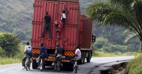 Des cyclistes et des piétons s'accrochent à un camion sur une route au Burundi. Crédit photo: REUTERS/Goran Tomasevic