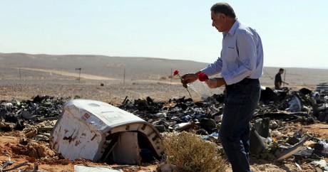 Un homme pose des fleurs sur les débris de l'Airbus A321 qui s'est crashé dans le Sinaï. Photo: REUTERS/Mohamed Abd El Ghany