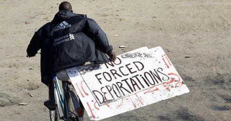 """Un migrant porte une pancarte avec l'inscription: """"pas de déportations forcées"""", à Calais. Photo: REUTERS/ Regis Duvignau"""