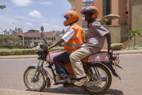 Un conducteur de boda-boda (moto-taxi) transporte un client à Kampala, le 6 mars 2015 AFP ISAAC KASAMANI