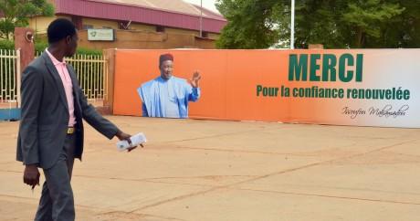 Un homme passe devant une bannière célébrant la réélection d'Issoufou au Niger, le 2 avril 2016. Crédit photo: AHEMED OUOBA/AFP