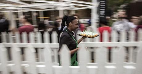 Une serveuse offre des rafraîchissements aux clients qui font la queue devant le Starbuks de Johannesburg, le 21 avril. AFP