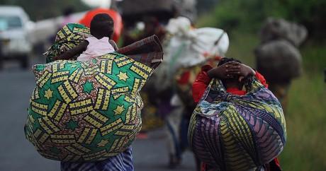 Des femmes fuient des combats sur la route entre Goma et Bukavu, en novembre 2012. TONY KARUMBA / AFP