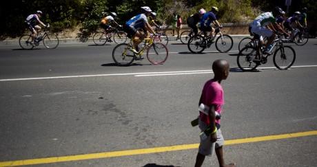 Un enfant marche près du peloton du Tour du Cap, en Afrique du Sud. RODGERBOSCH / AFP