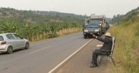Le président Museveni salue un automobiliste alors qu'il est arrêté sur le bord de la route.