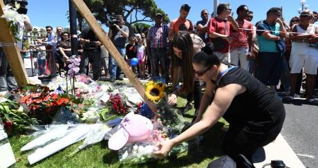 Une femme dépose des fleurs sur le mémorial installé près du lieu de l'attentat à Nice. BORIS HORVAT / AFP
