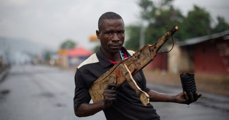 Un homme pose avec une arme factice en bois à Bujumbara au Burundi, le 5 mai 2015. PHIL MOORE / AFP
