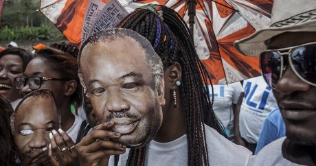 Un supporter d'Ali Bongo porte un masque à son effigie, le 23 août 2016 à Moanda. MARCO LONGARI / AFP