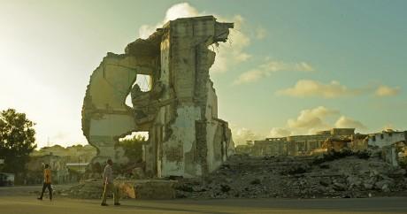 Un homme marche devant des ruines à Mogadiscio, le 11 août 2015. ABDIWAHAB MOHAMED / AFP