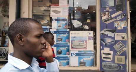 Un homme au téléphone devant un magasin hi-tech à Kampala, le 11 novembre 2011. MICHELE SIBILONI / AFP