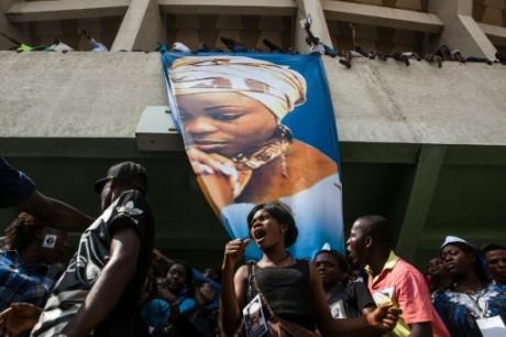 Une femme chante sous une bannière à l'effigie de la diva du gospel congolais Marie Misamu. Crédit photo AFP/Eduardo Soteras