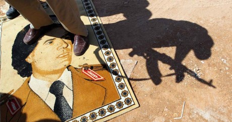 Un combattant des forces rebelles marche sur un portrait de Kadhafi le 4 octobre 2011 à Tripoli. KARIM SAHIB / AFP