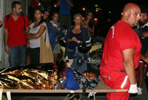 Des touristes regardent une femme, arrivée par bateau de Libye à Lampedusa, portée sur un brancart par un secouriste, dans la nuit du 4 août 2011 AFP Mauro Seminara