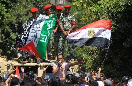 Des policiers font face à des manifestants qui brandissent les drapeaux égyptien et palestinien, le 20 août 2011 devant l'ambassade d'Israel au Caire AFP Khaled Desouki
