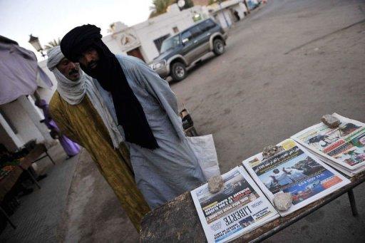 Deux hommes regardent, le 2 septembre 2011 à Djanet en Algérie, des quotidiens annonçant l'arrivée de Touaregs fuyant la Libye AFP/Archives Farouk Batiche