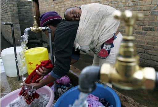 Une femme fait la lessive avec un bébé endormi sur son dos en Afrique du Sud en juin 2006. AFP/Archives Alexander Joe
