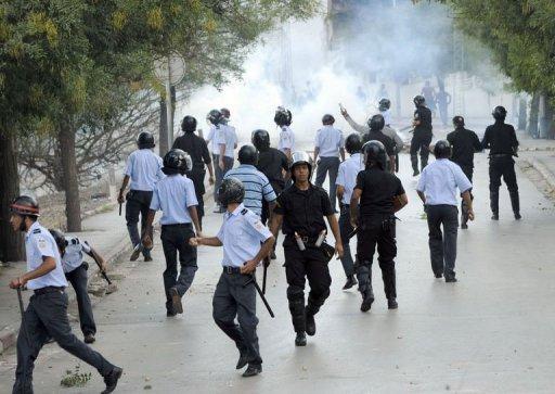 Des policiers tunisiens jettent des gaz lacrymogènes sur des manifestants le 14 octobre 2011 à Tunis. AFP Fethi Belaid