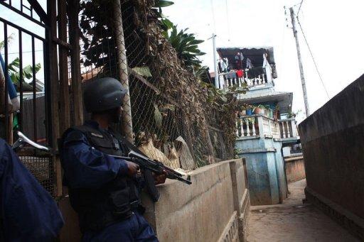 Un policier se met à l'abri pendant une mutinerie près de l'aéroport d'Antananarivo le 22 juillet 2012 AFP Andreea Campeanu