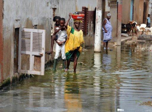 Des Sénégalais dans les rues inondées de Dakar, le 9 octobre 2008 AFP/Archives Georges Gobet