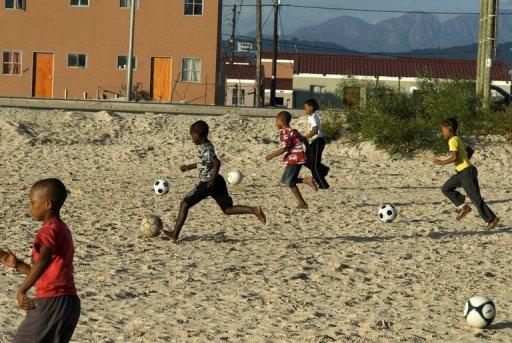 Des enfants jouent au football à l'est de Cape Town, en Afrique du Sud, en avril 2010 AFP/Archives Rodger Bosch